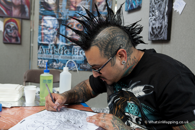 A tattoo artist sketches new designs at the 2012 Tattoo Convention in Tobacco Dock
